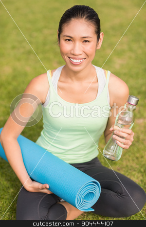 Sporty woman sitting with exercise mat and water bottle stock photo, Portrait of sporty woman sitting with exercise mat and water bottle in parkland by Wavebreak Media