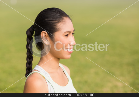 Smiling sporty woman looking away stock photo, Smiling sporty woman looking away in parkland by Wavebreak Media