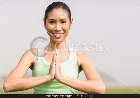 Smiling sporty woman doing yoga stock photo, Portrait of smiling sporty woman doing yoga in parkland by Wavebreak Media