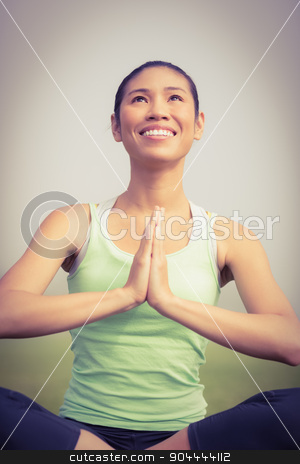 Smiling sporty woman doing yoga stock photo, Smiling sporty woman doing yoga in parkland by Wavebreak Media