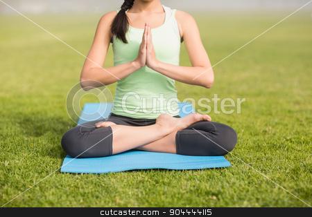 Sporty woman doing the lotus pose stock photo, Sporty woman doing the lotus pose in parkland by Wavebreak Media