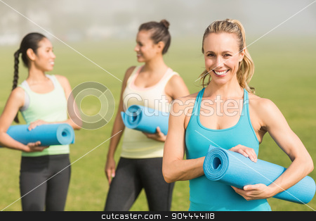 Smiling sporty blonde in front of friends stock photo, Portrait of smiling sporty blonde in front of friends in parkland by Wavebreak Media