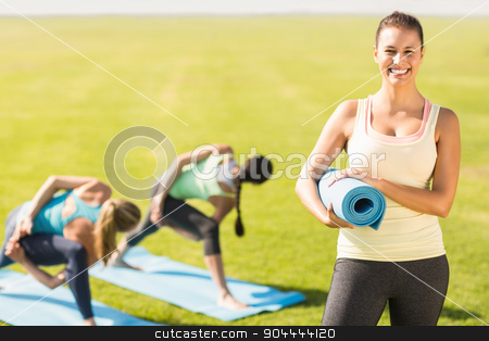 Smiling sporty brunette in front of friends doing exercises stock photo, Portrait of smiling sporty brunette in front of friends doing exercises in parkland by Wavebreak Media