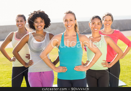 Smiling sporty women with hands on hips stock photo, Portrait of smiling sporty women with hands on hips in parkland by Wavebreak Media