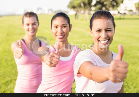 Smiling women wearing pink for breast cancer and doing thumbs up stock photo, Portrait of three smiling women wearing pink for breast cancer in parkland by Wavebreak Media