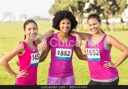 Three smiling runners supporting breast cancer marathon  stock photo, Portrait of three smiling runners supporting breast cancer marathon in parkland by Wavebreak Media