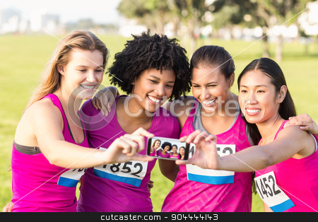 Runners supporting breast cancer marathon and taking selfies stock photo, Runners supporting breast cancer marathon and taking selfies in parkland by Wavebreak Media