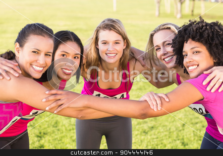 Five smiling runners supporting breast cancer marathon stock photo, Portrait of five smiling runners supporting breast cancer marathon in parkland by Wavebreak Media