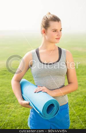 Sporty blonde holding exercise mat stock photo, Sporty blonde holding exercise mat in parkland by Wavebreak Media