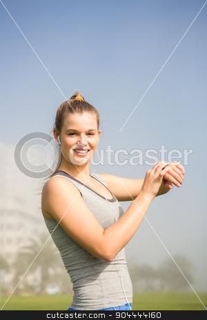 Smiling sporty blonde using smart watch stock photo, Portrait of smiling sporty blonde using smart watch in parkland by Wavebreak Media