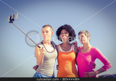 Sporty women posing and taking selfies with selfiestick  stock photo, Sporty women posing and taking selfies with selfiestick at promenade by Wavebreak Media