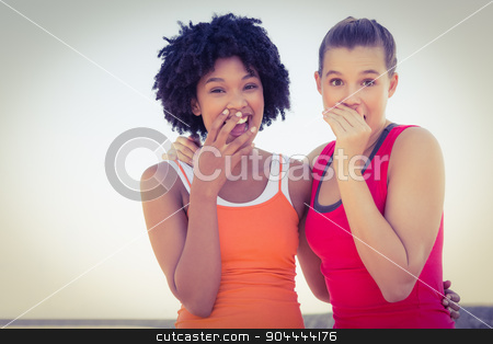 Two young women laughing to camera stock photo, Portrait of two young women laughing to camera at promenade by Wavebreak Media