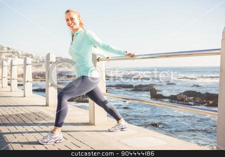 Smiling fit blonde stretching on railing stock photo, Portrait of smiling fit blonde stretching on railing at promenade by Wavebreak Media