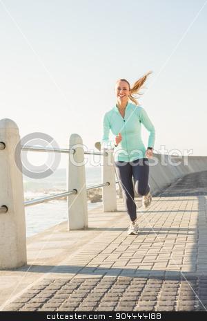 Smiling fit blonde jogging at promenade stock photo, Smiling fit blonde jogging at promenade on a sunny day by Wavebreak Media