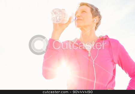 Sporty woman with headphones drinking water stock photo, Sporty woman with headphones drinking water at promenade by Wavebreak Media