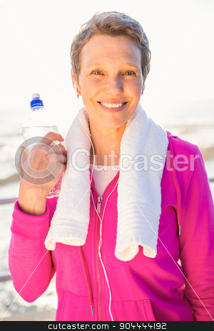 Smiling sporty woman with water bottle listening to music  stock photo, Portrait of smiling sporty woman with water bottle listening to music at promenade by Wavebreak Media