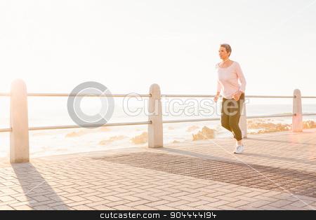 Sporty woman jogging at promenade stock photo, Sporty woman jogging at promenade on a sunny day by Wavebreak Media