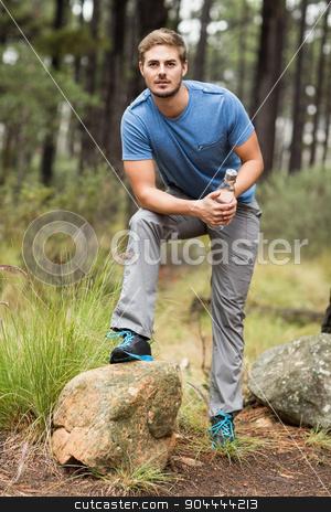 Portrait of a handsome man holding a water bottle stock photo, Portrait of a handsome man holding a water bottle in the nature by Wavebreak Media