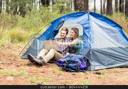 Young pretty hiker couple sitting in a tent looking at laptop stock photo, Young pretty hiker couple sitting in a tent looking at laptop in the nature by Wavebreak Media