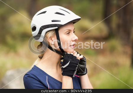 Young pretty happy biker taking off helmet stock photo, Young pretty happy biker taking off helmet in the nature by Wavebreak Media