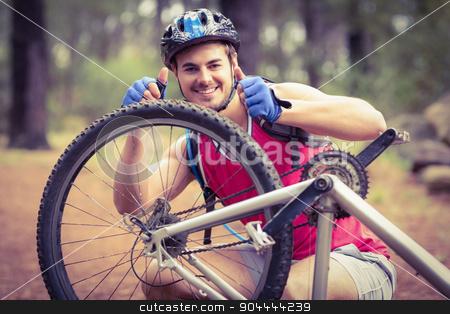 Happy handsome biker repairing bike showing thumbs up stock photo, Happy handsome biker repairing bike showing thumbs up in the nature by Wavebreak Media
