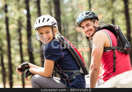 Young happy biker couple sitting on a rock stock photo, Young happy biker couple sitting on a rock in the nature by Wavebreak Media