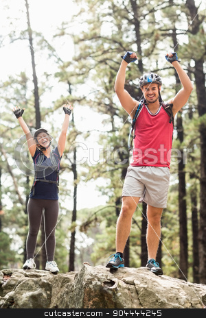 Young happy biker couple standing on a rock looking at the camer stock photo, Young happy biker couple standing on a rock looking at the camera in the nature by Wavebreak Media