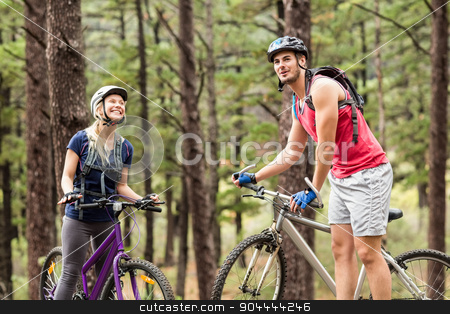 Young happy couple on bikes looking away stock photo, Young happy couple on bikes looking away in the nature by Wavebreak Media