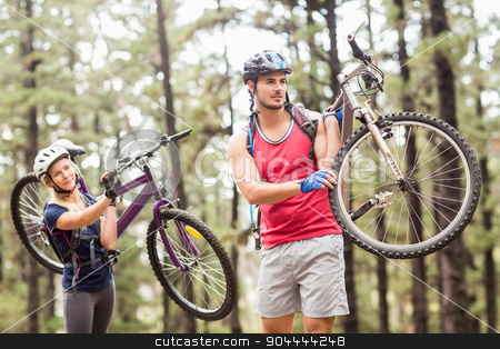 Young happy couple on bikes looking away carrying bikes stock photo, Young happy couple on bikes looking away carrying bikes in the nature by Wavebreak Media