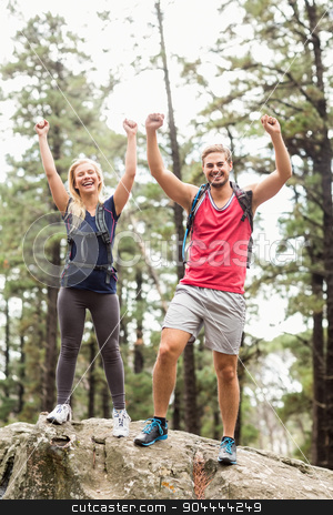 Happy young couple looking at camera with raised hands stock photo, Happy young couple looking at camera with raised hands in the nature by Wavebreak Media