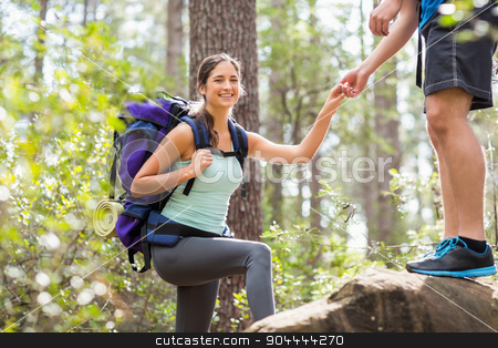 Happy hikers climbing on rock and smiling at camera stock photo, Happy hikers climbing on rock and smiling at camera in the nature by Wavebreak Media