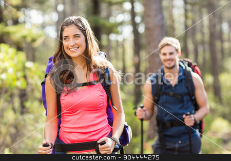 Young happy joggers hiking with trekking poles stock photo, Young happy joggers hiking with trekking poles in the nature by Wavebreak Media