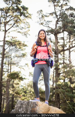 Young happy jogger standing on rock looking at camera stock photo, Young happy jogger standing on rock looking at camera in the nature by Wavebreak Media