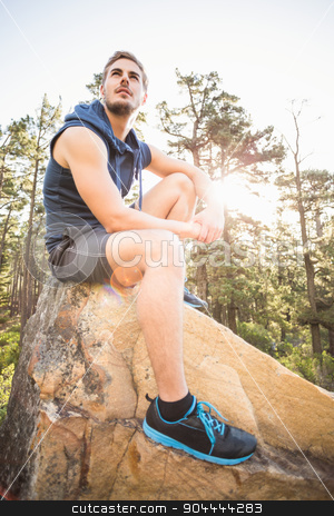 Young happy jogger sitting on rock and looking away stock photo, Young happy jogger sitting on rock and looking away in the nature by Wavebreak Media