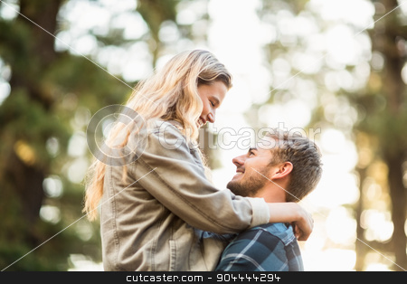 Smiling handsome man holding his girlfriend stock photo, Smiling handsome man holding his girlfriend in the nature by Wavebreak Media
