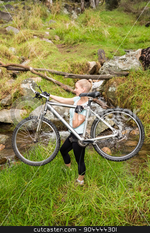 Side view of a fit woman lifting her bike stock photo, Side view of a fit woman lifting her bike in the nature by Wavebreak Media
