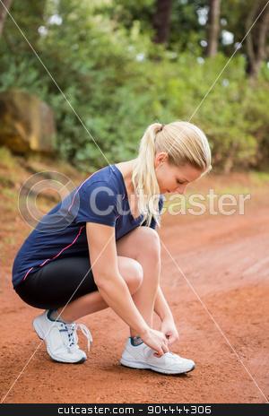 Athletic blonde tying her shoelace stock photo, Athletic blonde tying her shoelace in the nature by Wavebreak Media