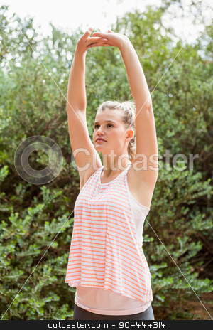Focused blonde athlete stretching arms stock photo, Focused blonde athlete stretching arms in the nature by Wavebreak Media