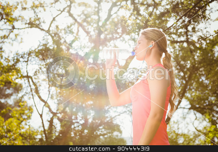 Blonde athlete drinking water out of bottle stock photo, Blonde athlete drinking water out of bottle in the nature by Wavebreak Media