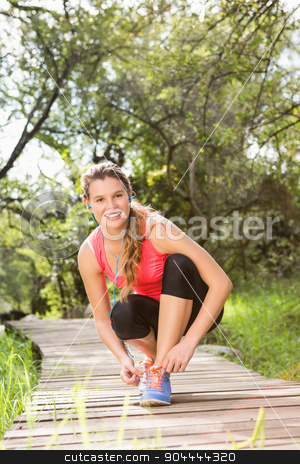 Smiling blonde athlete tying shoelace on wooden trail stock photo, Portrait of Smiling blonde athlete tying shoelace on wooden trail in the nature by Wavebreak Media
