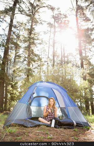 Pretty blonde camper smiling and sitting in tent stock photo, Portrait of pretty blonde camper smiling and sitting in tent in the nature by Wavebreak Media