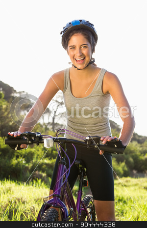 Smiling athletic brunette sitting on mountain bike stock photo, Portrait of smiling athletic brunette sitting on mountain bike in the nature by Wavebreak Media