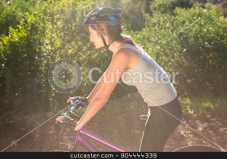 Athletic brunette mountain biking on path stock photo, Athletic brunette mountain biking on path in the nature by Wavebreak Media