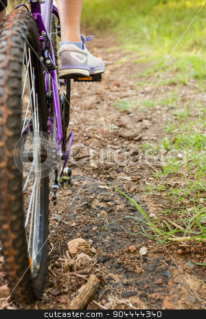 Close up view of woman pedaling on mountain bike stock photo, Close up view of woman pedaling on mountain bike in the nature by Wavebreak Media