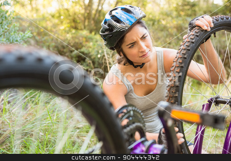 Athletic brunette checking her mountain bike stock photo, Athletic brunette checking her mountain bike in the nature by Wavebreak Media