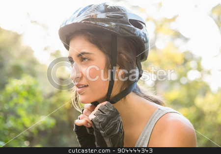 Athletic brunette putting on helmet  stock photo, Athletic brunette putting on helmet in the nature by Wavebreak Media