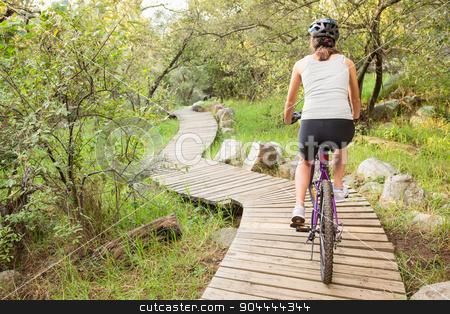 Rear view of athletic brunette mountain biking on wooden path stock photo, Rear view of athletic brunette mountain biking on wooden path in the nature by Wavebreak Media