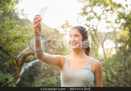 Smiling athletic brunette taking selfies stock photo, Smiling athletic brunette taking selfies in the nature by Wavebreak Media