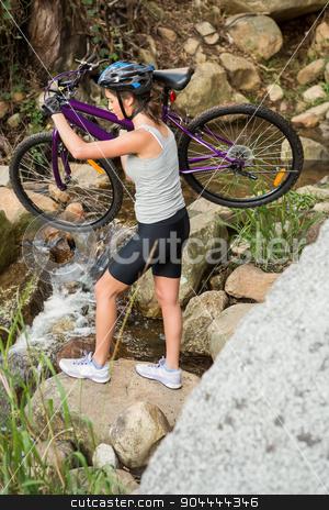 Athletic brunette carrying her mountain bike over stream stock photo, Athletic brunette carrying her mountain bike over stream in the nature by Wavebreak Media