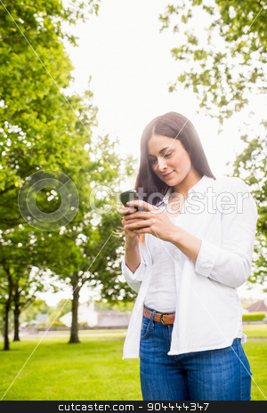 Beautiful brunette sending a text message stock photo, Beautiful brunette sending a text message on a sunny day by Wavebreak Media